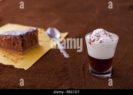 Poco taza de piccolo latte macchiato sobre una mesa cubierta con café molido como fondo y Brownie de chocolate con crema de cacao y virutas de coco