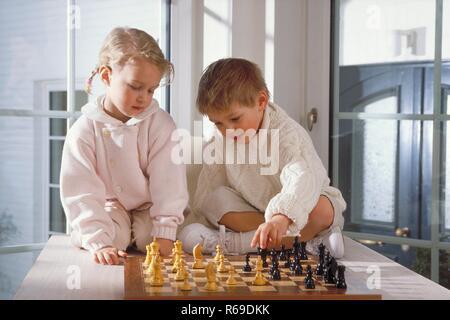 Retrato, Innenraum, Ganzfigur, rubias Maedchen und Junge, 4-5 Jahre alt, beide infierno gekleidet, sitzen auf dem Tisch und Schach spielen
