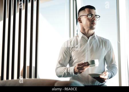 Joven empresario vistiendo franela blanca habiendo coffee break