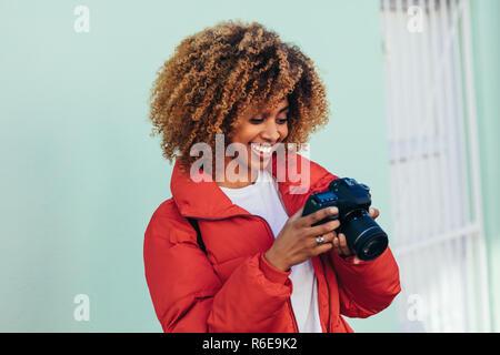 Alegre mujer afro americana de vacaciones tomando fotos de pie afuera. Retrato de un turista mujer mirando su cámara DSLR después de tomar una foto.