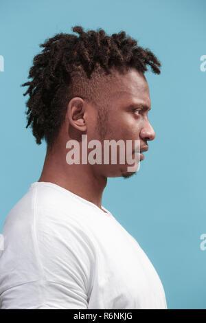 La empresa sorprendió al hombre afroamericano y permanente buscando fondo azul. Vista de perfil.