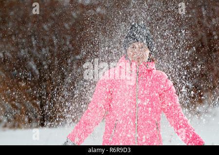 Mujer joven feliz jugando con la nieve en el parque. Concepto de invierno.