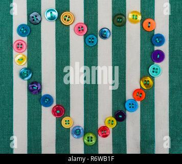 Amor corazón cosiendo botones sobre fondo de tela