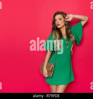 Hermosa joven grave en mini vestido verde está posando con sequin clutch y apartar la mirada. Tres cuartos de longitud studio shot backgroun en rojo