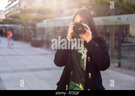 Atractivos turísticos mujer fotógrafo con cámara, al aire libre en las calles de la ciudad. Llamarada Solar Foto de stock