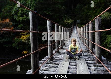 Un muchacho joven con camiseta amarilla sentado y meditando con los ojos cerrados en un puente colgante de madera, Wakayama, Japón