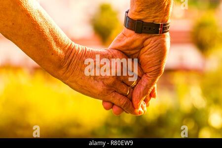 Captura recortada de la pareja de ancianos cogidos de la mano al atardecer al aire libre. Se centran en las manos