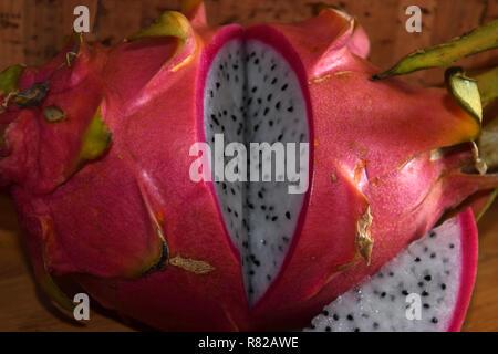 Rodajas de fruta del dragón, pitaya blanca o blanco-rosado y enriquecidos de tez madura también llamada fruta pitahaya Hylocereus undatus sobre mesa de madera