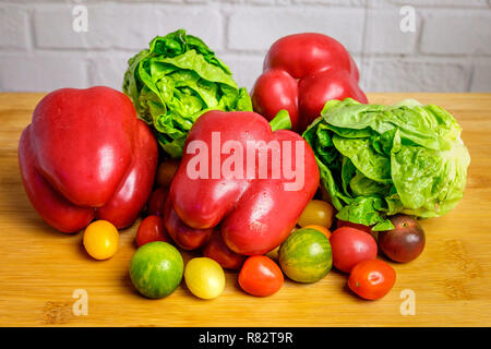 Pimientos rojos,lechuga romana y tomates cherry sobre un mostrador de madera delante de la pared de ladrillo blanco.