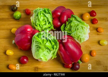 Ensalada verde fresco, pimientos y tomates cherry sobre fondo de madera