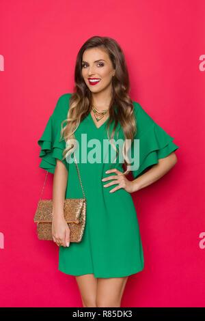Hermosa joven sonriente en mini vestido verde está posando con sequin clutch y mirando a la cámara. Tres cuartos de longitud studio shot en rojo