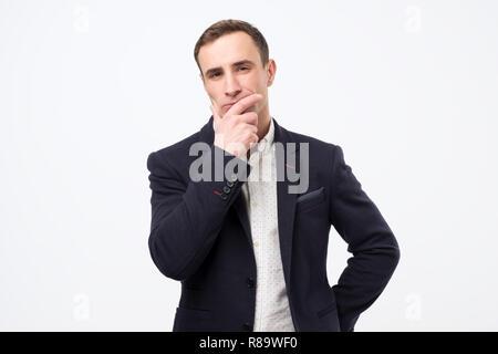 Pensativo hombre joven italiano está pensando en su trabajo. Foto de stock