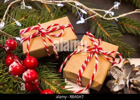 Dos envueltos en papel artesanal presenta el abeto natural con adornos de navidad, enfoque suave