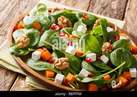 Alimentos saludables: ensalada fresca de la calabaza, las espinacas, el queso de cabra, nueces y semillas de granada closeup en una placa horizontal sobre la mesa.