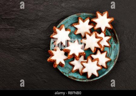 Navidad Zimtsterne tradicional alemán, almendra, chocolate y canela galletas de estrella, tomada desde la parte superior sobre un fondo oscuro con espacio de copia