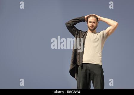 Guapo con barba, vistiendo ropa deportiva, moda hombre caucásico, hoodie negro y gris, camisa exterior soleada sobre fondo de cielo azul, espacio de copia