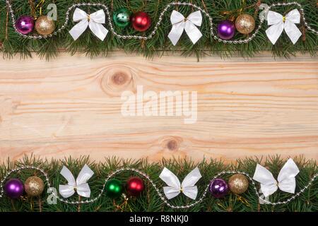 Bastidor de Navidad hechas de ramas de abeto blanco arcos decorados con cordones y bolas sobre un fondo de madera ligera