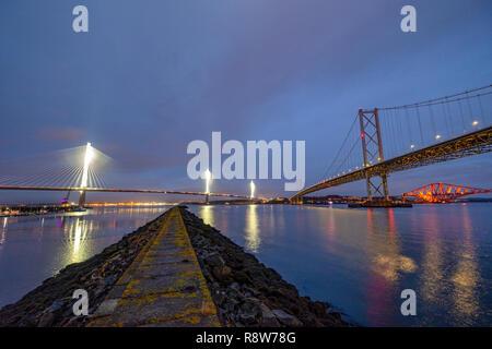 Ver al anochecer del nuevo cruce de Queensferry, puente Forth Road Bridge y el puente ferroviario de Forth desde Puerto Edgar South Queensferry. Foto de stock