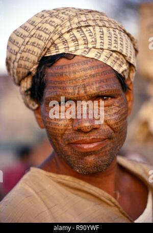 La cara tatuada de un asceta, Ramnaami pintados sobre tela con su mano pintada con el nombre del señor Ram atada alrededor de su cabeza como un turbante Foto de stock