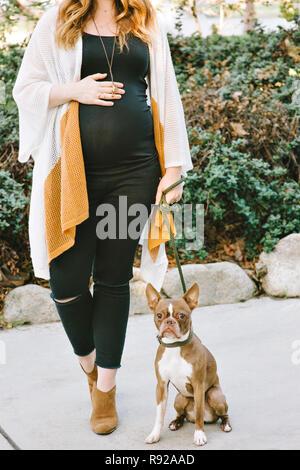 La mujer embarazada se encuentra junto a su mascota Boston Terrier y tiene sus manos sobre su vientre