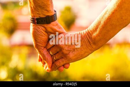 Captura recortada de la pareja de ancianos tomados de la mano exterior con la luz del atardecer. Se centran en las manos