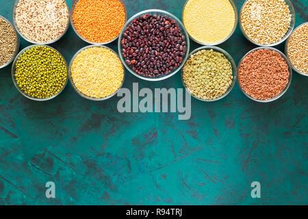 Recipientes de cristal con laicos plana fuentes alimenticias en esmeralda con textura de fondo cope con el espacio. Foto de stock