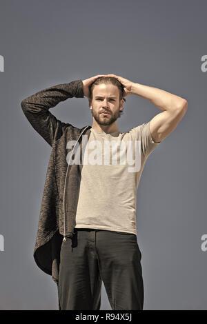 Moda hombre con barba, vistiendo ropa deportiva, moda hombre caucásico, hoodie negro y gris, camisa exterior soleada sobre fondo de cielo azul