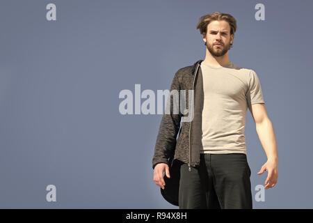 Hombre caucásico, hoodie negro y gris, camiseta, guapo con barba, vistiendo ropa de moda, soleada piscina sobre fondo de cielo azul, espacio de copia