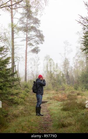 Mitad hombre adulto en un bosque nebuloso en Lerum, Suecia