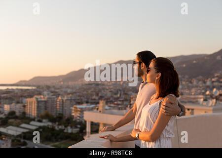 Disparo sideview horizontal de una joven pareja en atuendo de verano a disfrutar de la ciudad y vistas a la montaña desde la terraza de la azotea. Copie el espacio.