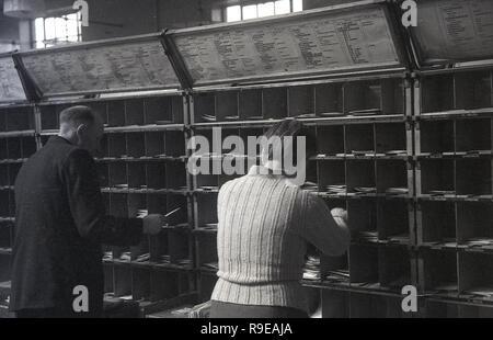 1948, dos Royal Mail workng personal dentro de una oficina de clasificación postal, Inglaterra, Reino Unido. La imagen muestra las letras puedan poner en pequeños cubículos para las distintas calles. Foto de stock
