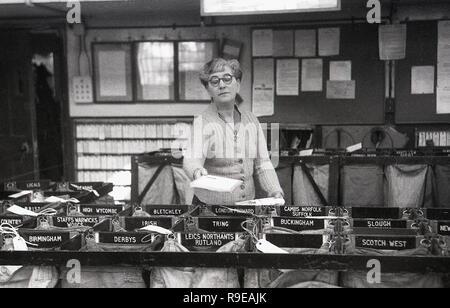 1948, dentro de una oficina de clasificación postal de Royal Mail, la imagen muestra una trabajadora poniendo letras en sacos individuales para las diferentes ciudades y regiones del Reino Unido. Foto de stock