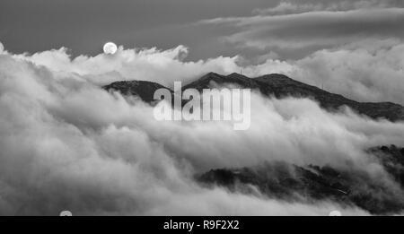 Full Moon comenzó a elevarse por encima de las montañas Troodos cubiertas de noche fogy nubes. Foto de stock