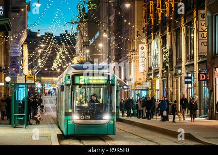 Helsinki, Finlandia - Diciembre 6, 2016: El tranvía sale desde la parada en la calle Aleksanterinkatu. La noche de Navidad Navidad Año Nuevo Calle festiva Illumina Foto de stock