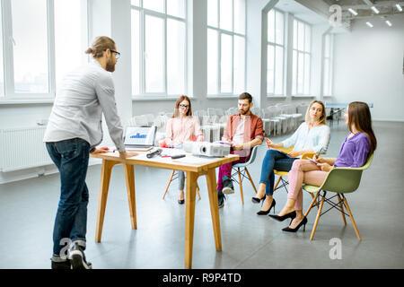 El hombre como un altavoz informando a la audiencia de jóvenes durante la reunión en la sala de conferencia Foto de stock