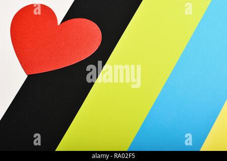 Tarjeta del Día de San Valentín. Corazón de papel rojo sobre fondo de colores, vista superior. El amor y el concepto de vacaciones. Símbolo del amor y coloridas rayas.