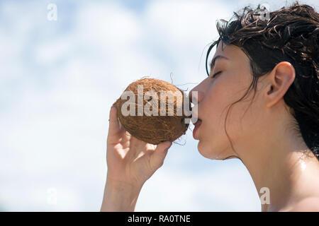 Limpieza de la dieta, comer vegetariano o vegano. Mujer es hidratante su piel con una crema de coco leche de coco.. beber cócteles en la playa. Mujer bebiendo cocon