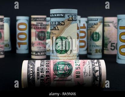 Dólar. Rollo de billetes de dólar en otras posiciones. Moneda americano en junta de negro. Rollos de billetes de dólar americano en todas las denominaciones aisladas en