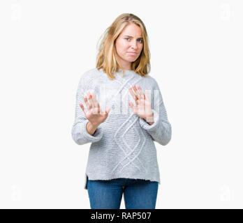 Hermosa joven vistiendo un suéter de invierno más antecedentes aislados disgustado expresión, disgustado y temeroso haciendo asco cara porque aversión