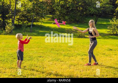 Madre e hijo jugando con una gran maqueta avión de juguete en el parque Foto de stock