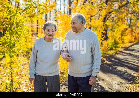 Feliz seniors en el otoño bosque. La familia, la edad, la estación y el pueblo concepto - feliz pareja senior caminar sobre fondo de árboles de otoño