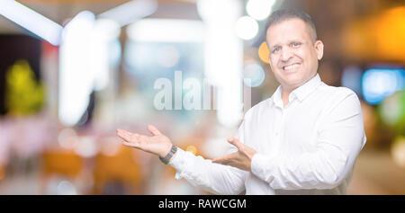 Edad media árabe hombre elegante sobre antecedentes aislados que invitan a entrar sonriendo naturales con la mano abierta