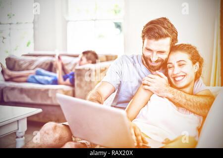 Feliz pareja sentada en un sofá y utilización portátil Foto de stock