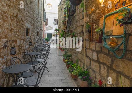 Cafe mesas y sillas fuera en la vieja calle acogedora en Split, Croacia, Dalmacia