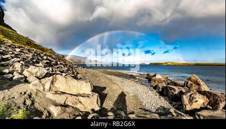 Arco iris sobre el famoso dinosaurio en Staffin Bay en la isla de Skye. Foto de stock