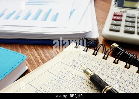 Cifras financieras en un libro de contabilidad y negocios gráficos analíticos.