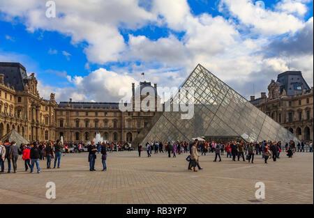París, Francia - 25 de octubre de 2013: Los turistas caminando delante de la pirámide y el famoso Museo del Louvre, uno de los museos de arte más grande del mundo un