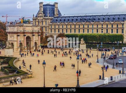 París, Francia - 25 de octubre de 2013: Los turistas caminando delante del famoso Museo del Louvre, uno de los museos de arte más grande del mundo y un histórico monumen