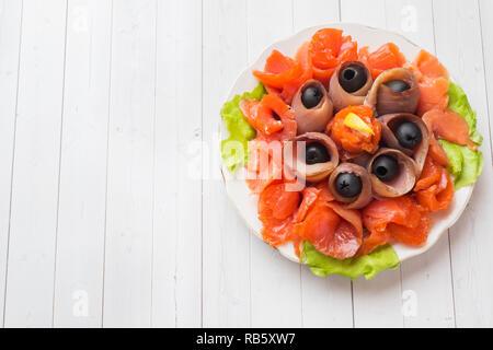 Restaurante gourmet que sirve un plato de sal ahumada, filetes de pescado crudo blanco y salmón. Manjar exquisito plato de marisco fresco con el bagre, carne de salmón con olivos