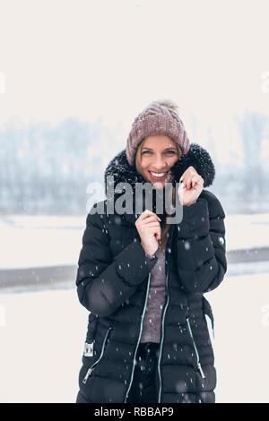 Mujer sonriente en clima frío mientras la nieve cayendo.
